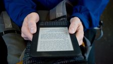 Image of an ebook reader and hands, reading on public transit