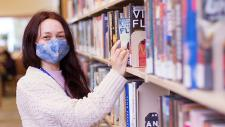Woman wearing a mask browses books on a library shelf