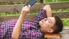 Man lying down and reading on device outside