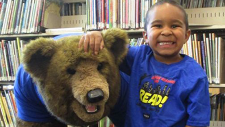 Boy with bear in matching Summer Reading shirts