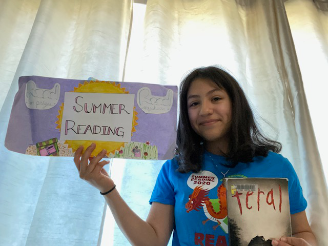 Young volunteer, holding sign for Summer Reading