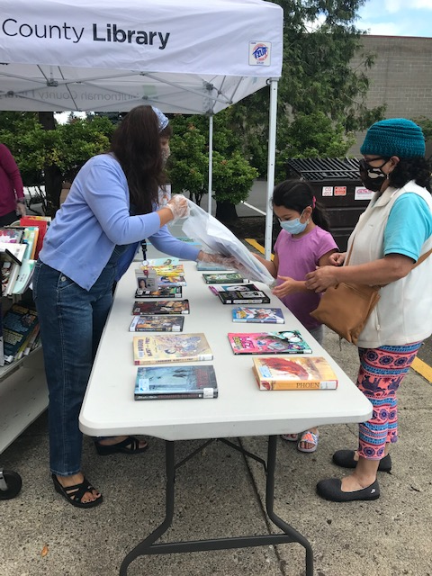 Librarian hands out books at library summer lunch program at Gresham Library