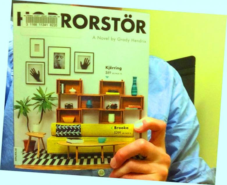 Photo of Ross holding a copy of Horrorstor