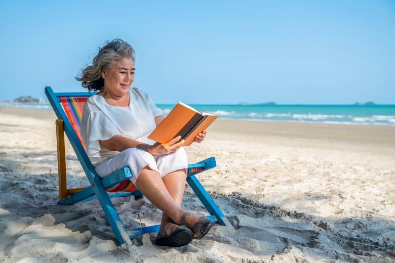 Woman reading book in a beach chair by ocean