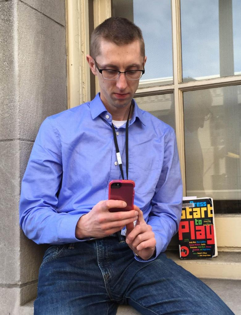 Photo of Ross on cell phone, with copy of Press Start to Play