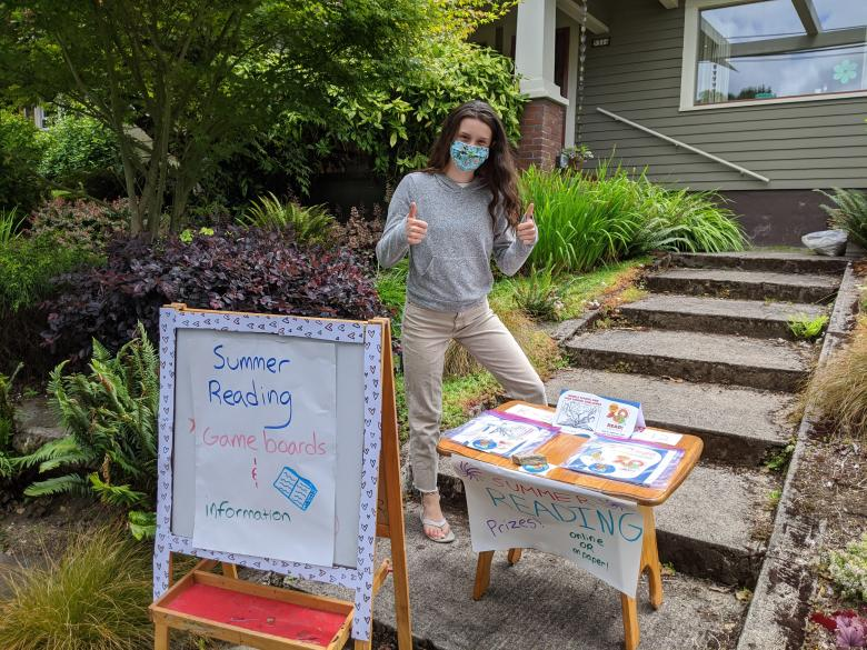 Summer Reading volunteer with cardtable with books and sign on sidewalk promoting Summer Reading