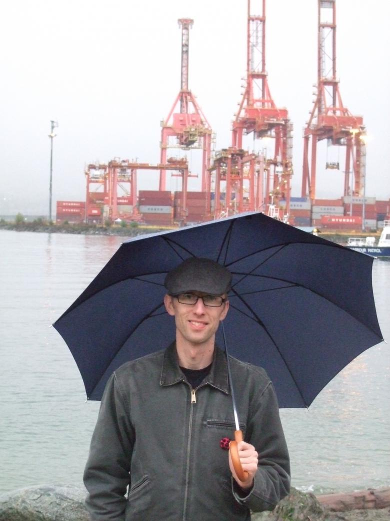 Photo of Ross in front of some cranes.