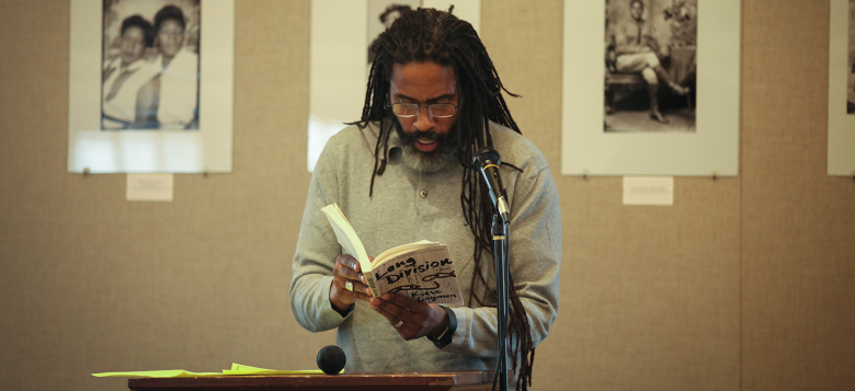 Man standing and reading from a book