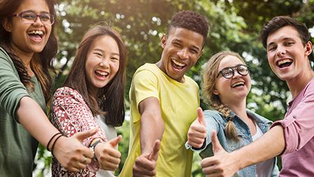 Cinco estudiantes sonriendo y haciendo el gesto de aprobación