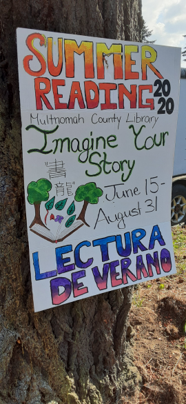 Sign on tree trunk about Summer Reading 2020