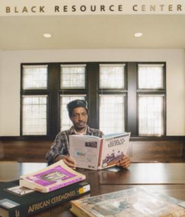 Mr. Obie Hill reading a book at Black Resource Center