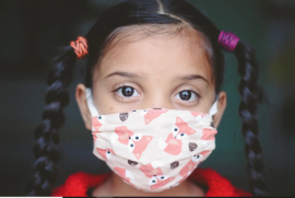 closeup on the face of a young child with mask on