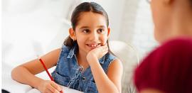 Una niña escribe con un lapiz y escucha a alguien fuera de la foto