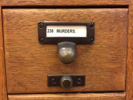 "Card catalog drawer reading ""murder"""