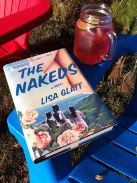 Photo of The Nakeds by Lisa Glatt resting on a lawn chair with a summer cocktail
