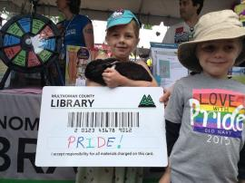 Two children, their pet rabbit, and a giant library card at the Portland Pride Festival.