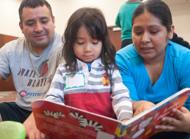 Mother and father help their daughter to read.