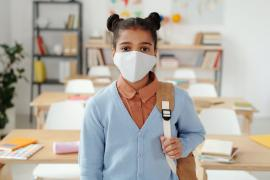 Young student in classroom with mask on