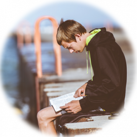 Boy sitting on a dock reading a book