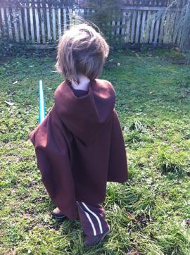 Photo of child in brown hooded play cape