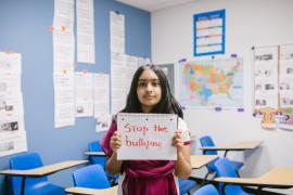 """young person in a classroom holding a sign that reads, """"Stop the bullying"""""""