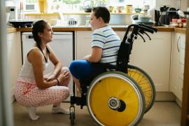 Boy in wheelchair talking to a woman in the kitchen