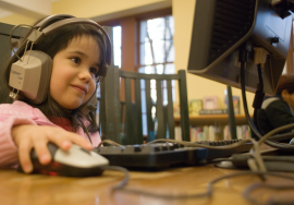 Child using a computer with headphones