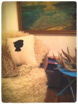 Photo of corner clutter: oil painting, pillows, anters, books