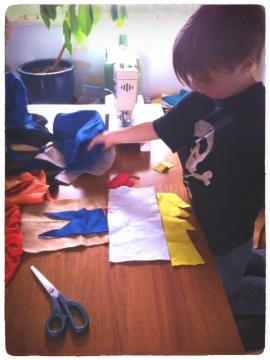 Photograph of a young boy arranging fabric in preparation to sew.