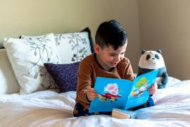 a Latino boy, 5 or 6 years old, sits on a bed and reads a book.  He is smiling.