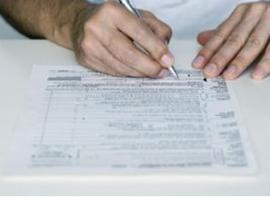 hands filing out tax form