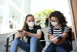two students sitting outside of school on steps, looking at schoolwork, with masks on