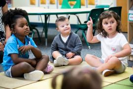 three preschool age kids - two girls and one boy - sit on the carpet.  The boy has the facial characteristics of Downs Syndrome.  One girl has her hand raised.