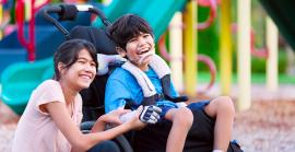 Two children at playground, holding hands, one child is in a mobility device.