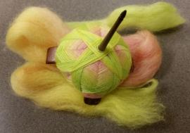 A Kuchulu spindle with multicolored yarn.