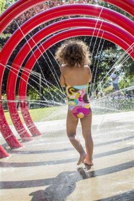 Little girl playing in splash pad.