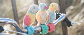 Knitted birds on bike handlebars