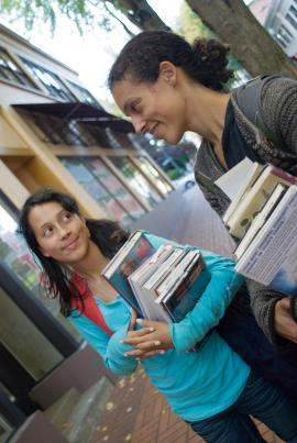 Two women holding stacks of library books