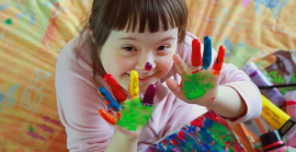 Young child with paint on hands, smiling up at camera.