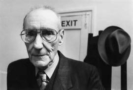 A black and white picture of William Burroughs.  In the backgroud is a hat on a hook and an exit sign.