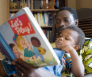 Child and adult reading book