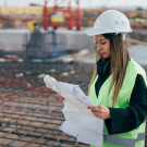 Image of woman in a hardhat reading building plans on a construction site
