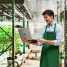 Image of man holding a laptop while standing next to racks of cannabis plants